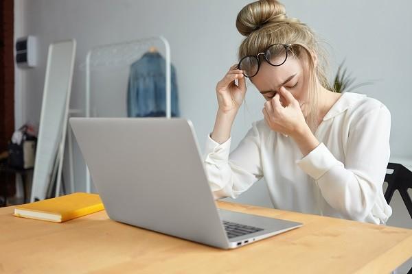 Junge Frau sitzt am Schreibtisch und reibt sich erschöpft die Augen